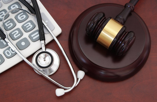 Gavel, calculator and stethoscope on wooden table