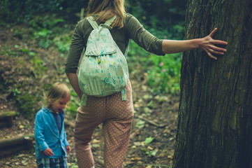 Mother and toddler relaxing by a tree in the woods
