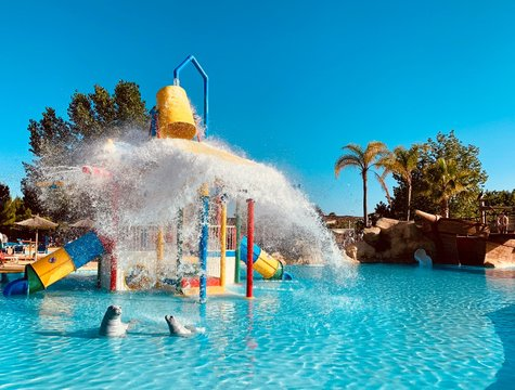 A swimming pool for children in a water park.  There is a big bucket that throws water from above.