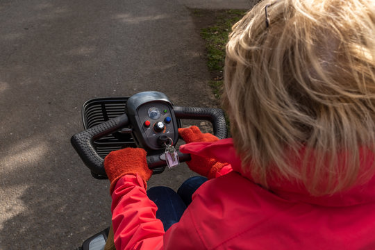 An over the shoulder shot of an elderly lady in a red coat enjoying the freedom of an electric mobility scooter, three quarters of the head showing