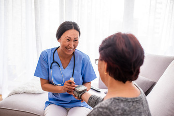 Portrait of young Asian nurse with elderly woman. Helpful volunteer taking care of senior lady at healthcare home. Picture of a senior lady with her friendly caregiver.
