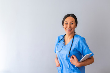 Portrait of confident young Asian female doctor. Portrait of a good looking young nurse with tablet computer in a grey background. Doctor with stethoscope around his neck looking at the camera
