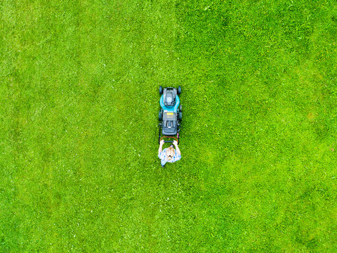 Beautiful girl cuts the lawn. Mowing lawns. Aerial view beautiful woman lawn mower on green grass. Mower grass equipment. Mowing gardener care work tool. Close up view. Aerial lawn mowing