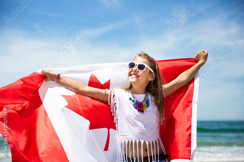 Happy girl carries Canadian flag on Canada Day, July 1
