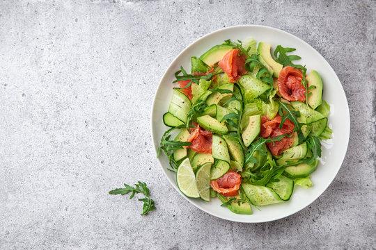 avocado, smoked salmon and cucumber salad on white plate