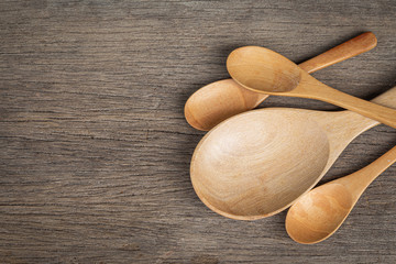 Wooden spoon and wooden ladle on a wooden background