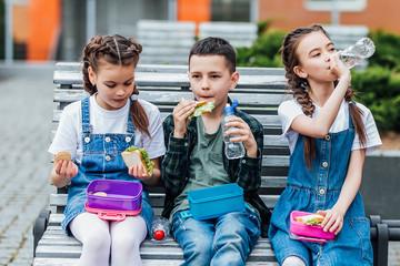 Group of children during break time having lunch or breakfast are having fun.