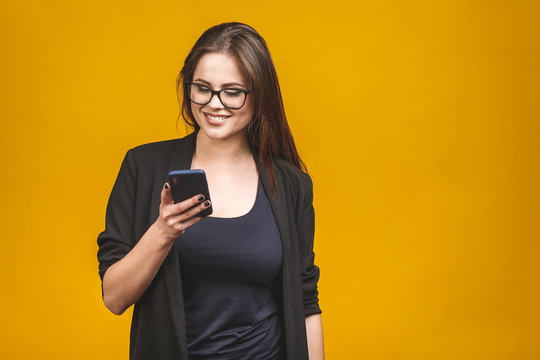 Portrait of smiling business woman in eyeglasses holding smartphone and looking back over yellow background. Using phone.