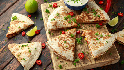 Mexican quesadilla with chicken, corn, black beans, cheese, vegetables, lime and yogurt sauce on wooden board
