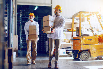 Two blue collar workers in white uniforms and with yellow helmets on heads relocating heavy boxes...
