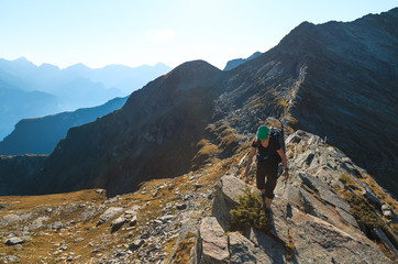 Fotomurales - Female hiker on a narrow ridge in the mountains. Via Alta Verzasca, Switzerland.