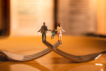 Happy Family and Work Life Balance Concept. Miniature of Father, Mother and Son holding Hands and...