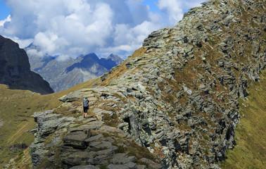 Female hiker on a narrow ridge in the mountains. Via Alta Verzasca, Switzerland.
