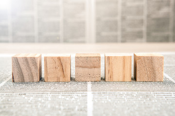 Five wooden cube blocks on a newspaper background