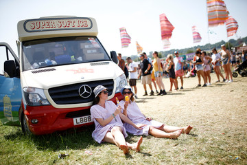 Festival goers rest next to an ice cream truck during Glastonbury Festival in Somerset