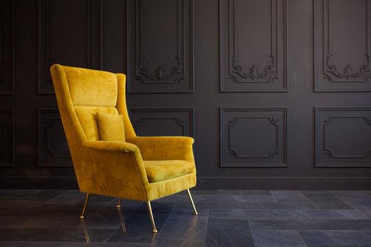 Stylish bright yellow chair against a dark gray wall