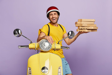 Happy male involved in customer service, picks up pizza, wears helmet, yellow t shirt, carries rucksack, poses near scooter, being energetic and fast, waits for customers near office, transports food
