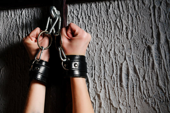 BDSM outfit for adult sex games. Close-up of female hands handcuffed bondsge to the bars