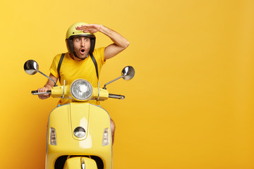 Stupefied male motorbike driver in ptotective helmet, keeps hand near forehead, focused with astonishment into distance, gazes something shocking, isolated on yellow wall. People and riding. Fototapete