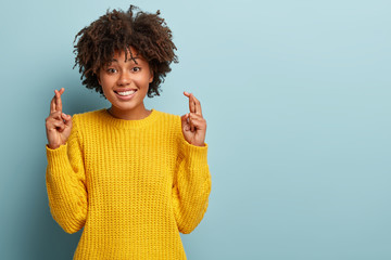 Wish and anticipation concept. Beautiful dark skinned lady stands with crossed fingers, dreams party went well, prays dream fulfill, has pleasant toothy smile, wears yellow jumper blank space on right