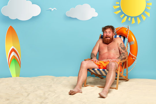 Frightened bearded redhead man gets sunburned at comfortable beach chair, has red skin, needs protective lotion, surfboard, lifebuoy and sea in background. Summer time, holidays and sunbathing concept