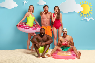 Five mixed race friends stare into distance, pose together at sandy beach with swimming supplies, wears swimsuits and shorts, summer sunny day. People, friendship and recreation time concept