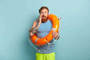 Beach safeguard man in sailor vest and green shorts, works at sea resort, has stupefied facial expression, touches cheek, stands inside of orange lifebuoy. Swimmer under supervision of instructor