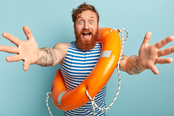 Friendly looking happy man with ginger hair and thick beard, gives hug at camera, stands with life preserver, wears striped sailor vest, says hello summer, isolated on blue. Water rescuing concept