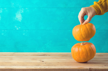 Autumn background with pumpkin on wooden table and woman hand.
