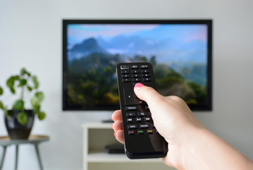 Watching TV. A woman's hand holding the TV remote control with a television in the background. Nature, documentary, tv screen, binge watching