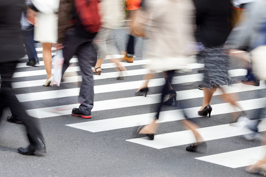 People crossing a street in motion