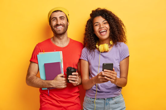 Teen students have happy expressions, spend free time together, prepare for exams, hold textbooks, takeaway coffee, mobile phone, dressed in casual apparel, discuss project, isolated on yellow wall