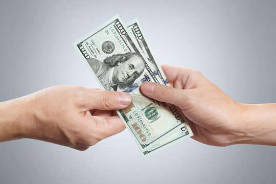 Hands sharing dollars on gray background