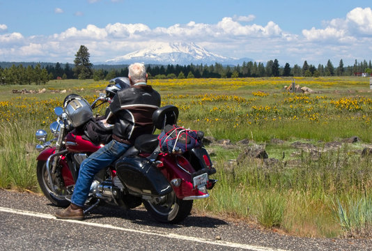 Motorcyclist parked looking at mountain scenery