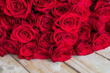 Obraz Bukiet czerwonych róż na drewnianym  stole - fototapety do salonu