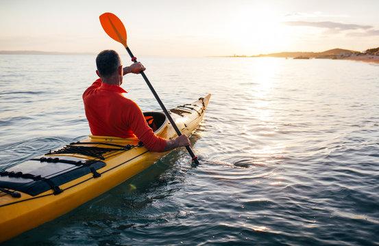 Senior man paddling kayak on the sunset sea