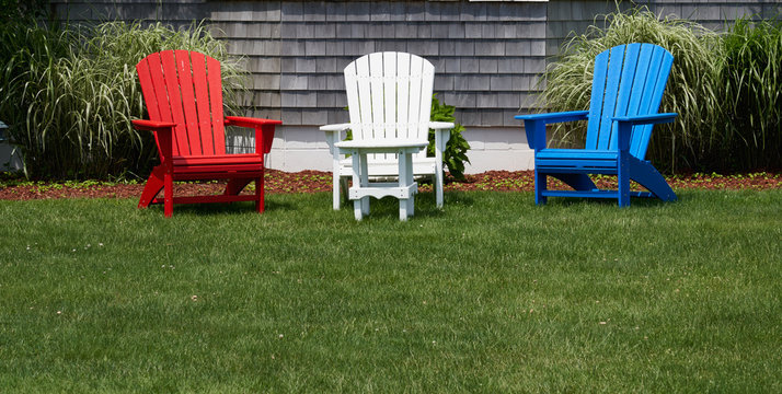 red white and blue wooden adirondack chairs on a green lawn in front of a house