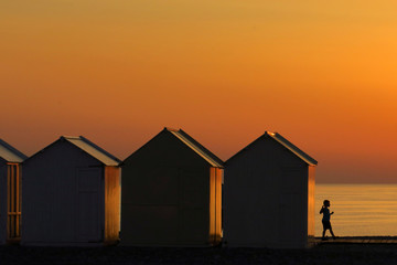 A child walks beside beach cabins on a pebbled beach, during sunset as a heatwave hits France, in Cayeux-sur-Mer