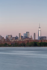 Downtown Manhattan with WTC from east river at sunrise with long exposure