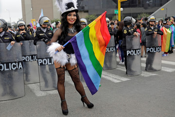 A drag queen stands in front of Peruvian Police during the gay pride parade in Lima