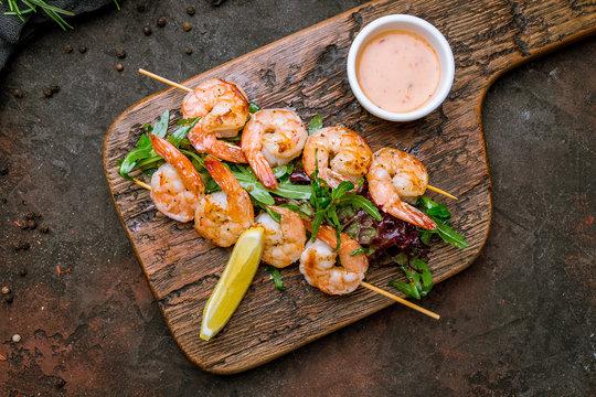 tiger shrimp kebab on the board on dark concrete rustic background
