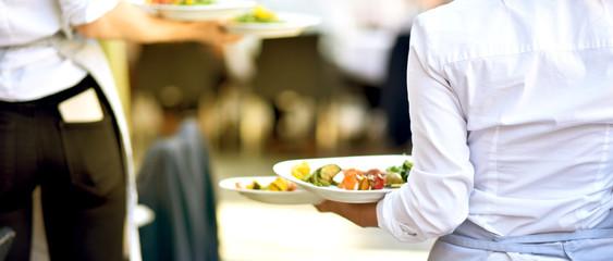 Fototapeta Bedienung serviert Essen für die Gäste im Restaurant obraz