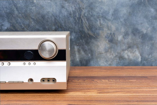 Half front side AV receiver with volume and AUX Plugin on wood table