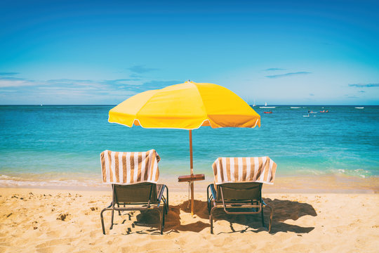 Beach holiday lounging chairs under sun umbrella vacation background. Summer tropical travel destination.