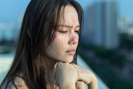 Sad woman depressed on her balcony.