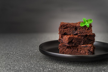 Dark chocolate and cocoa brownie fudge cakes dessert with mint against black and grey stone...