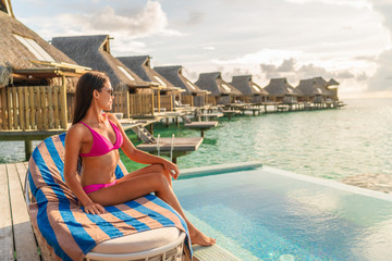 Wall Mural - Luxury hotel vacation woman relaxing on private overwater bungalow infinity swimming pool resort room.