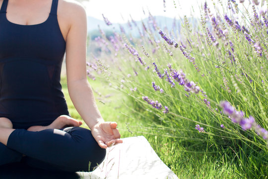 Woman is practicing yoga in lavender field. Girl is meditating, sitting in lotus pose outdoors. Sport workout at nature. Concept of healthy lifestyle, wellbeing. Female fitness classes. Close up