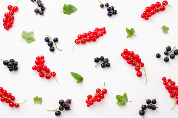 Red and black currants on white background