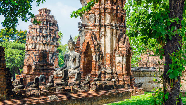 Only intact ancient Buddha statue among the destroyed statues in Ayutthaya historical park, Thailand.